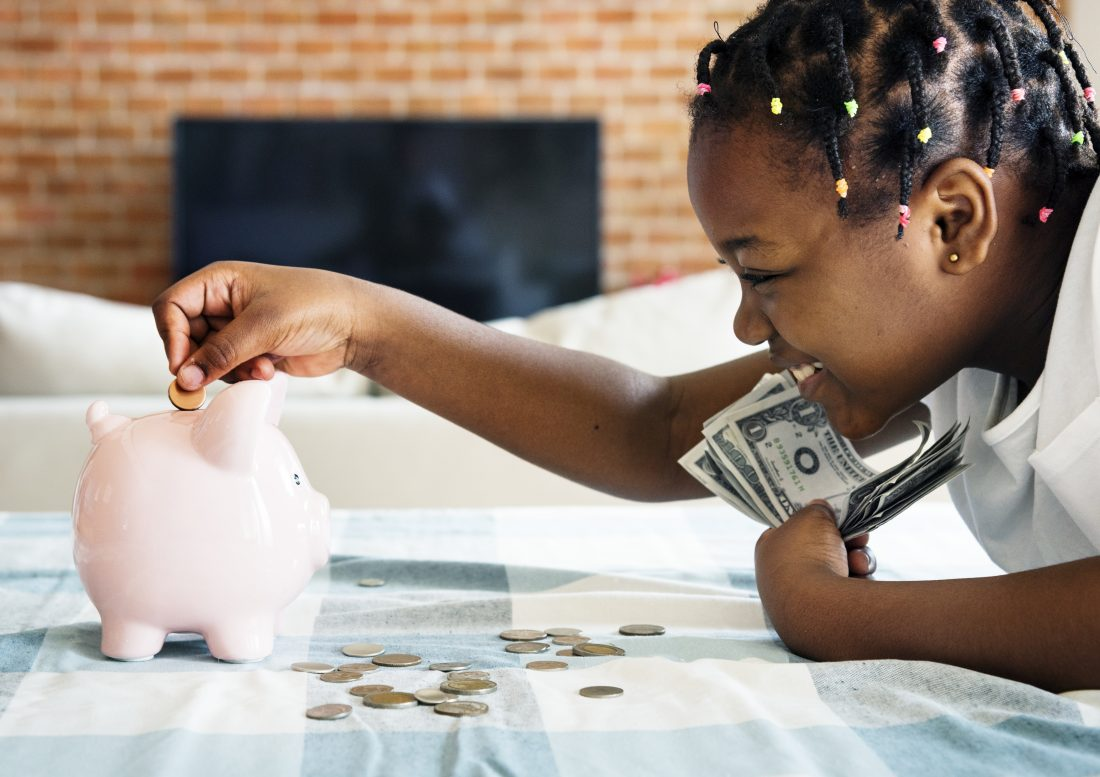 little girl putting money into her piggy bank